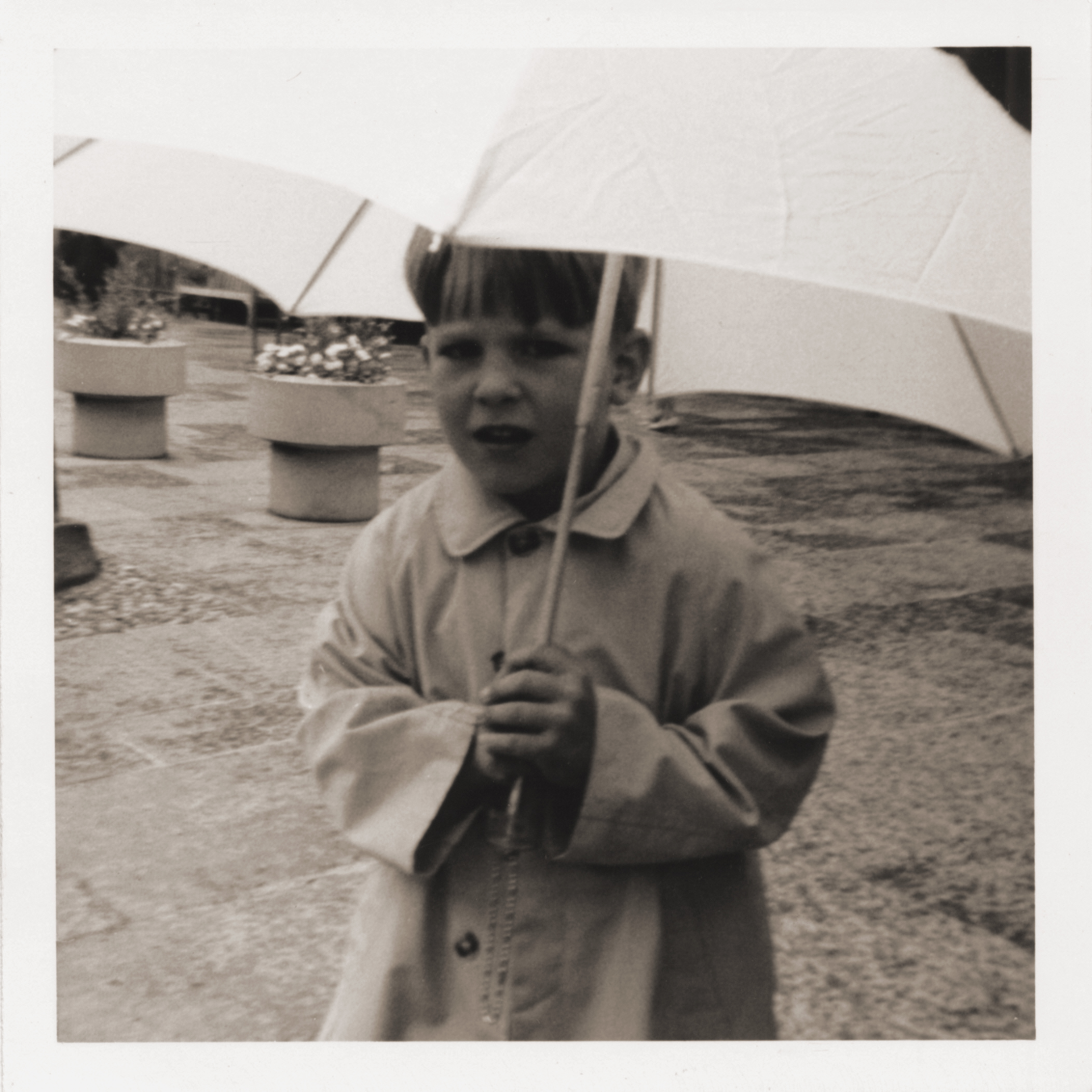 Black and white snapshot of a small boy holding a white umbrella, with pavement and flower pots behind him.