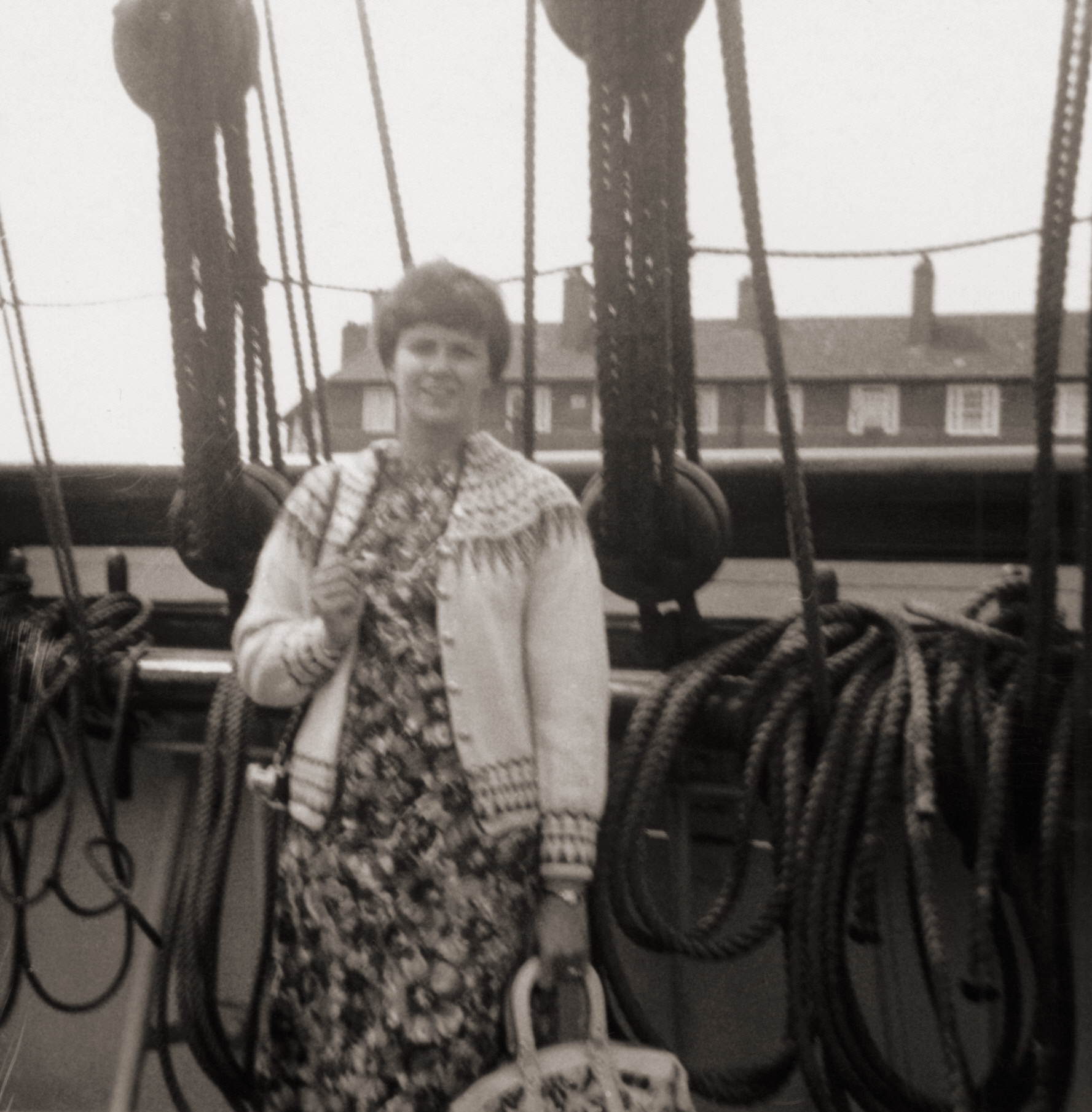 Black and white snapshot of a woman in a Norwegian sweater on the deck of a ship.